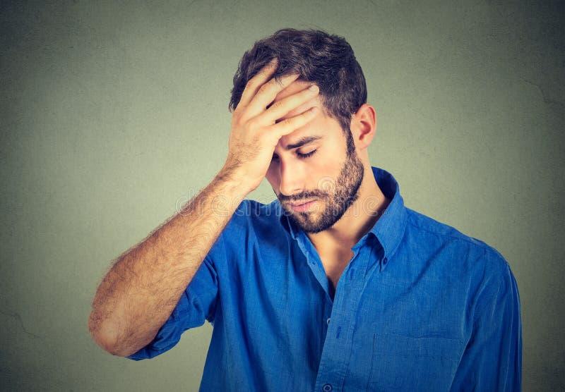 Stressad ledsen ung man som ser ner på grå väggbakgrund royaltyfri foto