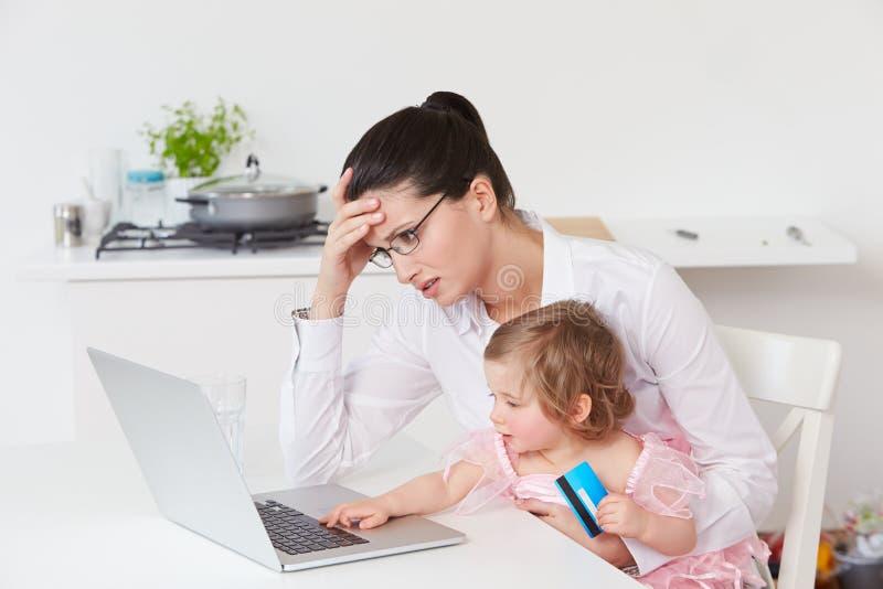 Stressad moder med barnet som hemma använder bärbara datorn royaltyfria foton