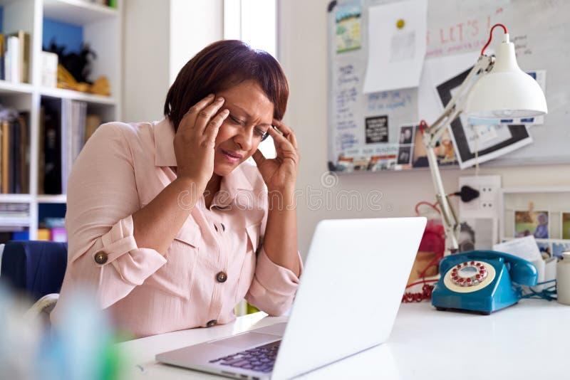 Stressad mogen kvinna med bärbar datorarbete i inrikesdepartementet arkivbilder