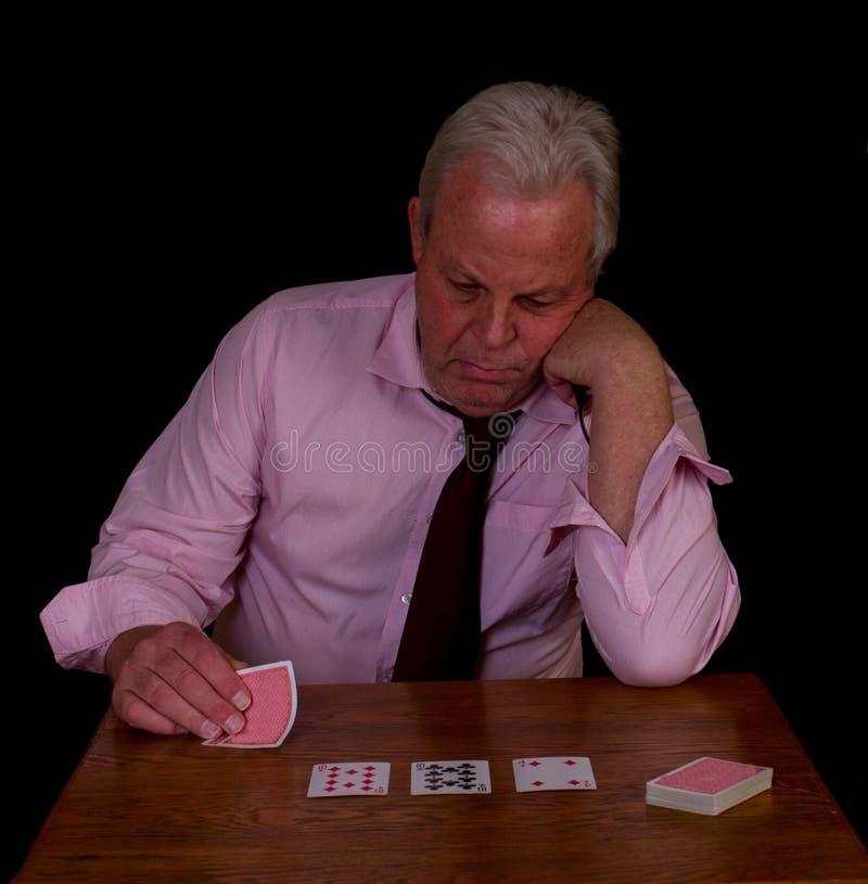 Stressad seende äldre man som spelar poker royaltyfria foton