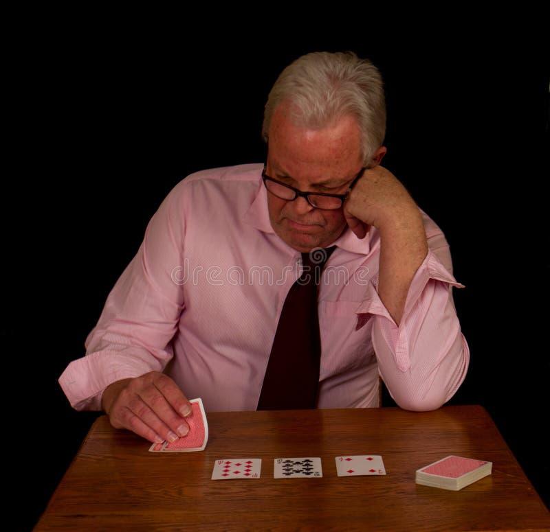 Stressad seende äldre man som spelar poker fotografering för bildbyråer