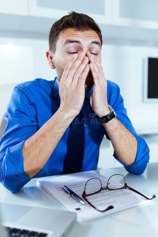 Stressad stilig ung affärsman, medan arbeta med bärbara datorn i kontoret royaltyfri bild