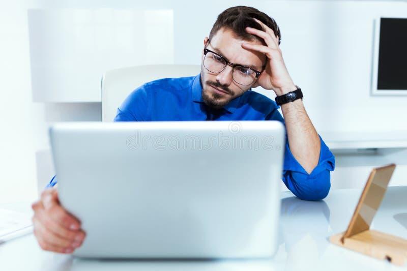 Stressad stilig ung affärsman, medan arbeta med bärbara datorn i kontoret arkivbilder