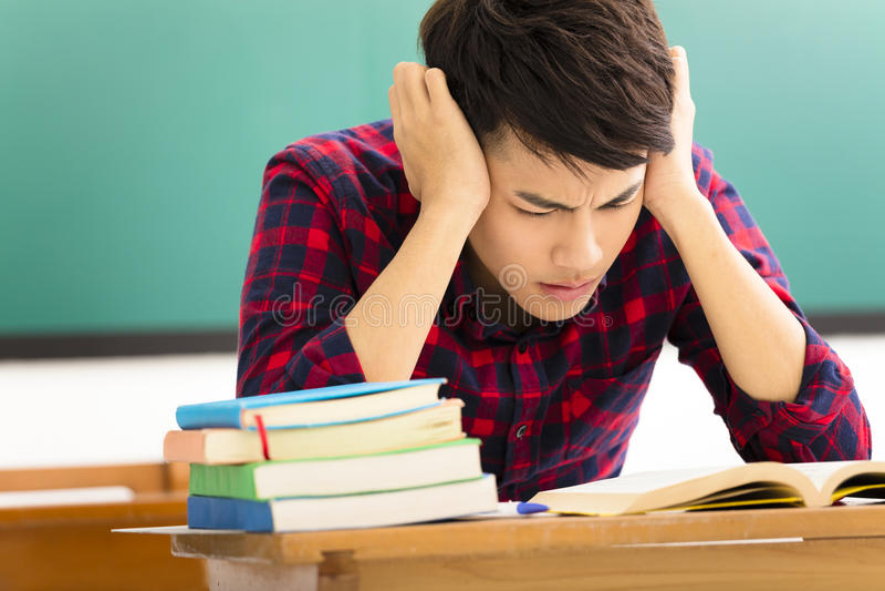 Stressad student som studerar för examen i klassrum royaltyfri foto