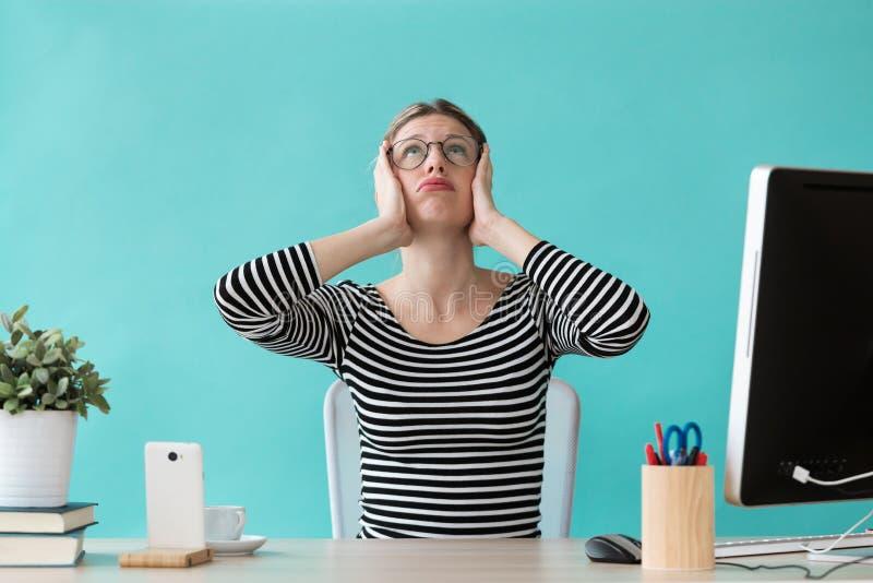 Stressad ung kvinna som rymmer hennes huvud och ser till upp, medan arbeta i kontoret arkivfoton