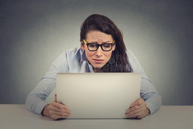 Stressad ung kvinna som ser datoren royaltyfri bild