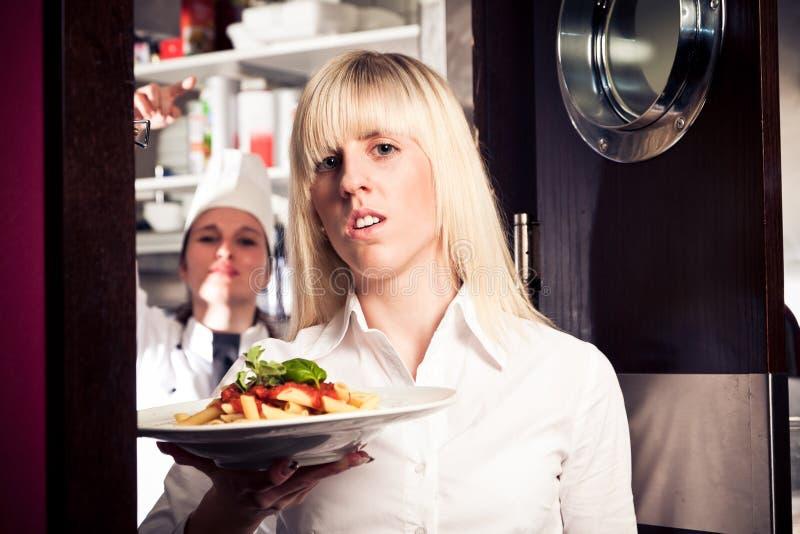 Stressad uppassare Coming Out Of köket royaltyfria foton