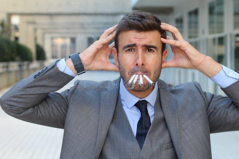 Stressad ut affärsman som samtidigt röker fyra cigaretter arkivbilder