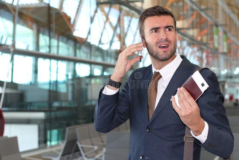 Stressad ut affärsman under en påringning på flygplatsen arkivbild