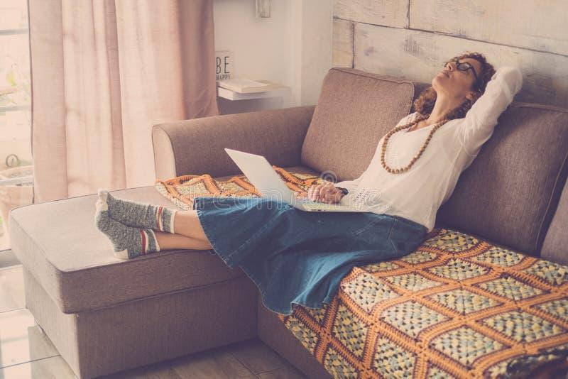 Stressad ut härlig mellersta ålderkvinna som hemma arbetar på bärbara datorn på soffan alternativt kontor för internet för online arkivfoton