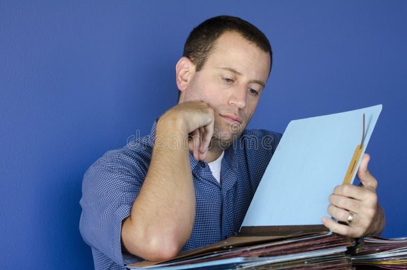 Stressad ut man på arbetsläsning till och med mappar royaltyfri foto