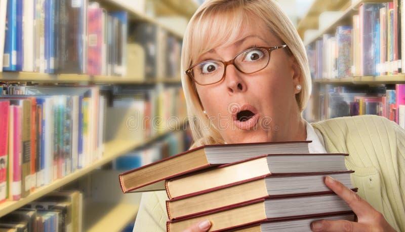 Stressad uttrycksfull bibliotekarie, student eller lärare Juggling Books i arkiv royaltyfri bild
