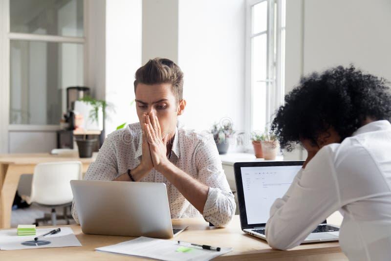 Stressade arbetare som direktanslutet läser nyheterna för företagskonkurs royaltyfria foton