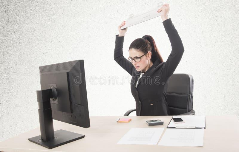 Stressat affärskvinnasammanträde på tabellen framme av datorer arkivbild