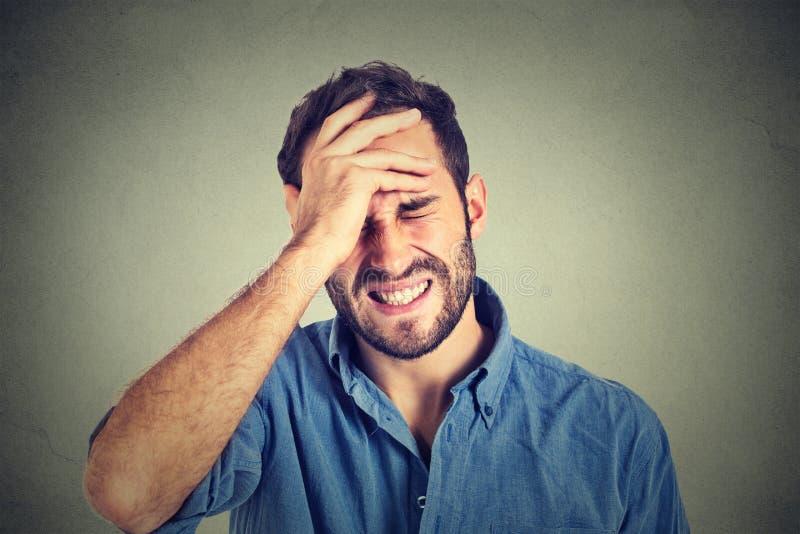 Stressat manlidande från huvudvärken som isoleras på grå väggbakgrund royaltyfri fotografi