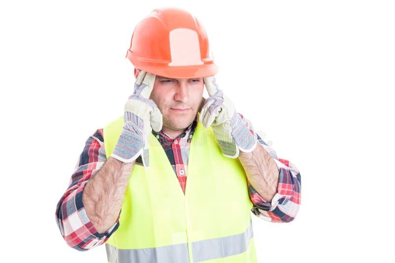 Stressat manligt byggmästarelidande från huvudvärk royaltyfria bilder