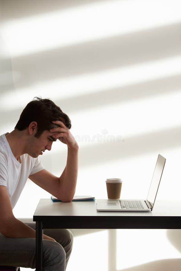 Stressat manligt högskolestudentUsing Computer In klassrum arkivbilder