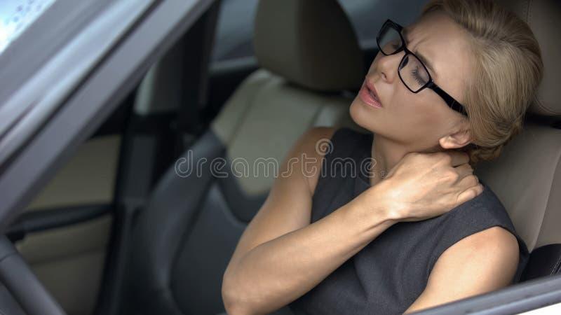 Stressat obehag för affärskvinnalidandehals, sammanträde i bil, stillasittande liv royaltyfria foton