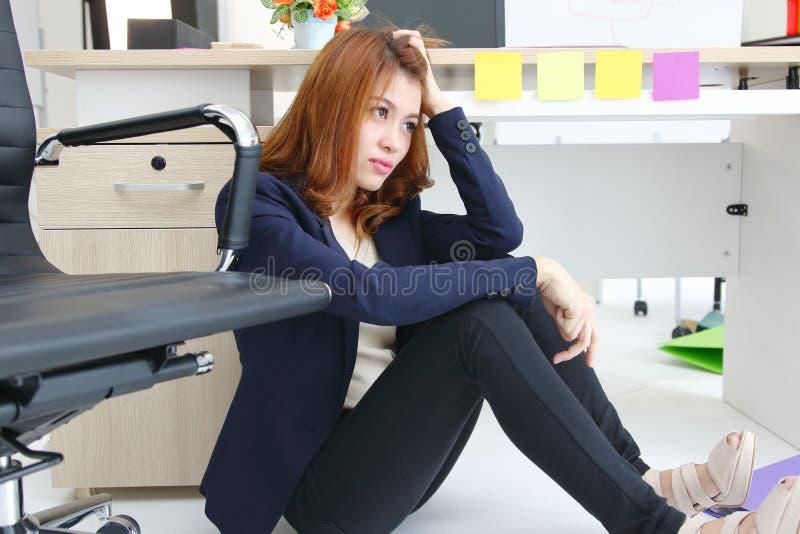 Stressed在办公室工作场所疲倦了年轻亚裔女商人坐地板和感觉的消沉 库存照片