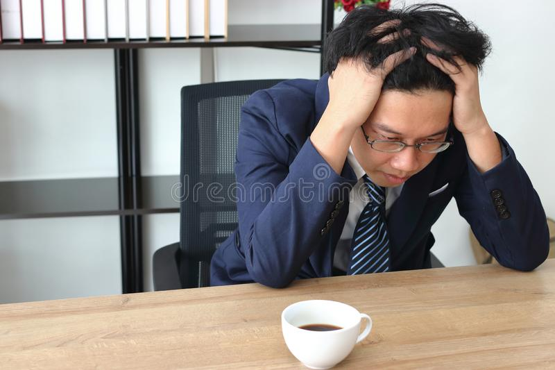 Stressed在办公室工作场所疲倦了年轻亚裔商人用在面孔感觉消沉的手 免版税图库摄影