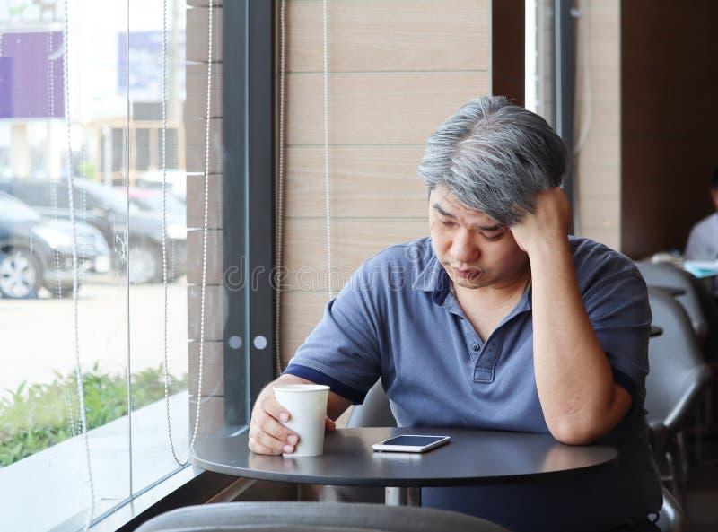 Stressed疲乏的年轻亚裔中年人,老人作为手在头感觉消沉和被用尽的坐由窗口在 图库摄影