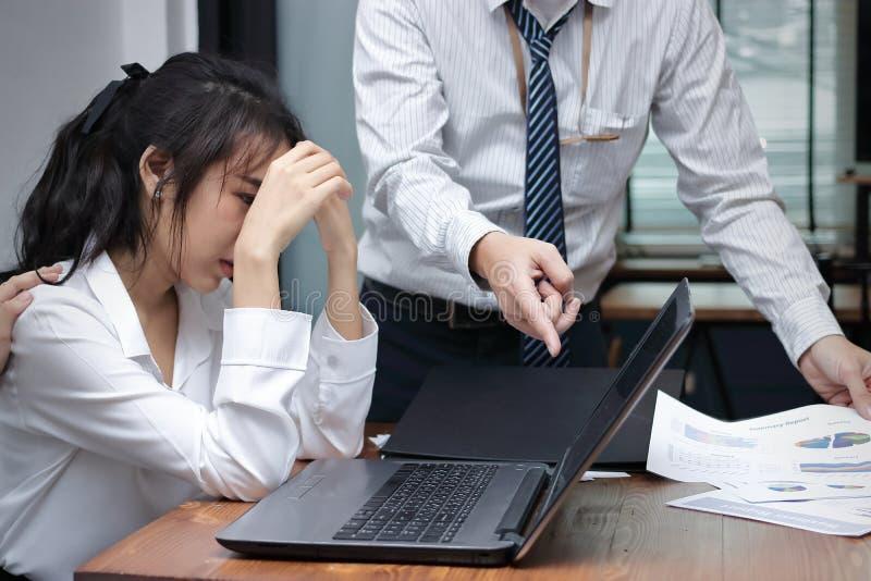 Stressed在办公室工作场所压下了年轻亚裔女商人责备与上司 免版税库存照片
