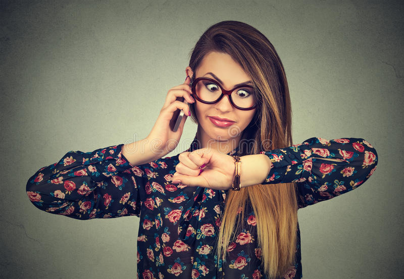 Stressed a étonné la femme d'affaires regardant la montre-bracelet, fonctionnant tard pour se réunir photographie stock
