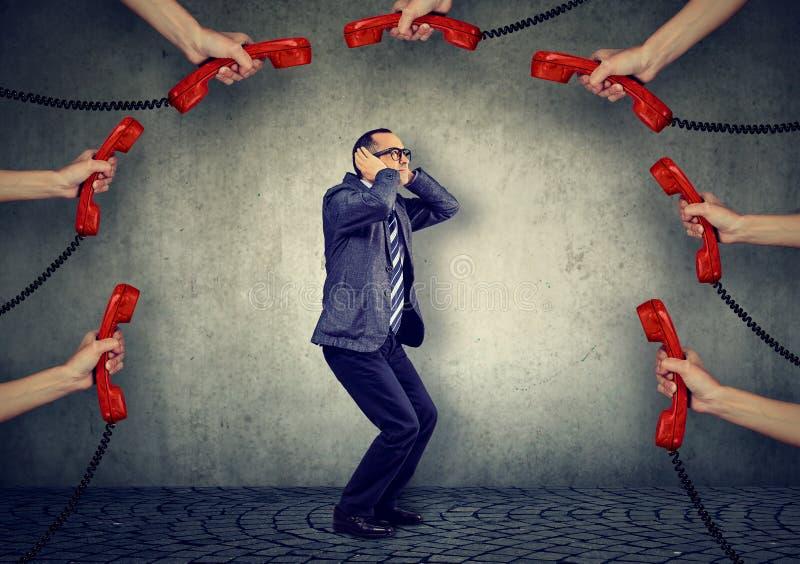 Stressed überlastete durch zu vielen Telefonanrufgeschäftsmann stockfoto