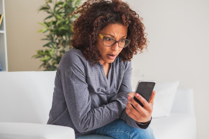 Stressed сотряс молодое телефонное сообщение чтения чернокожей женщины стоковые фотографии rf