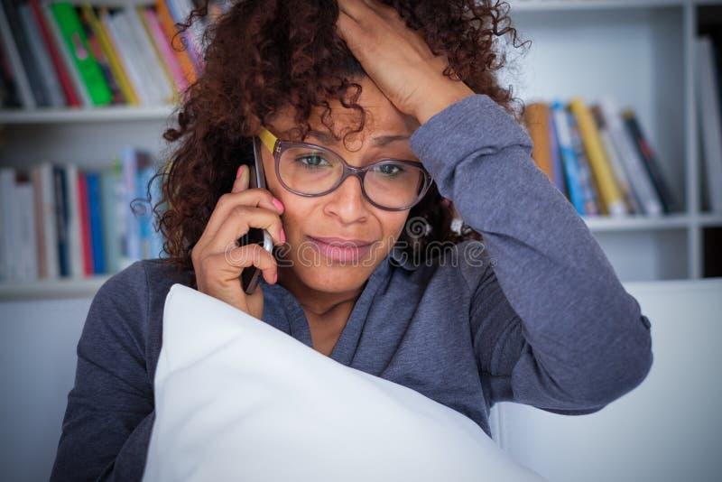 Stressed сотряс молодую чернокожую женщину говоря на клетчатом