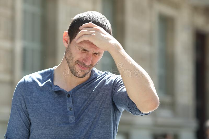 Stressed adult man suffering headache in the street. Stressed adult man complaining suffering headache touching head in the street royalty free stock photo