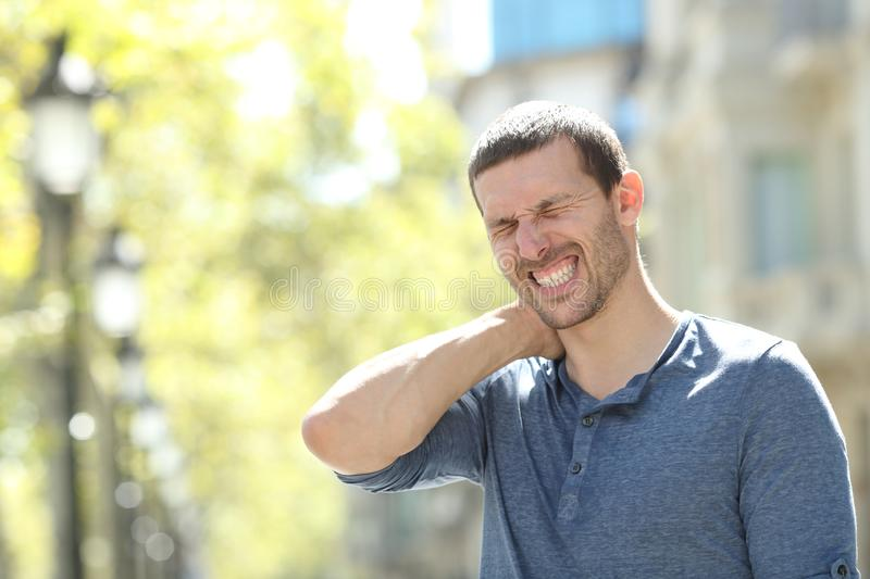 Stressed adult man suffering neck ache in the street. Stressed adult man suffering neck ache standing alone in the street royalty free stock image