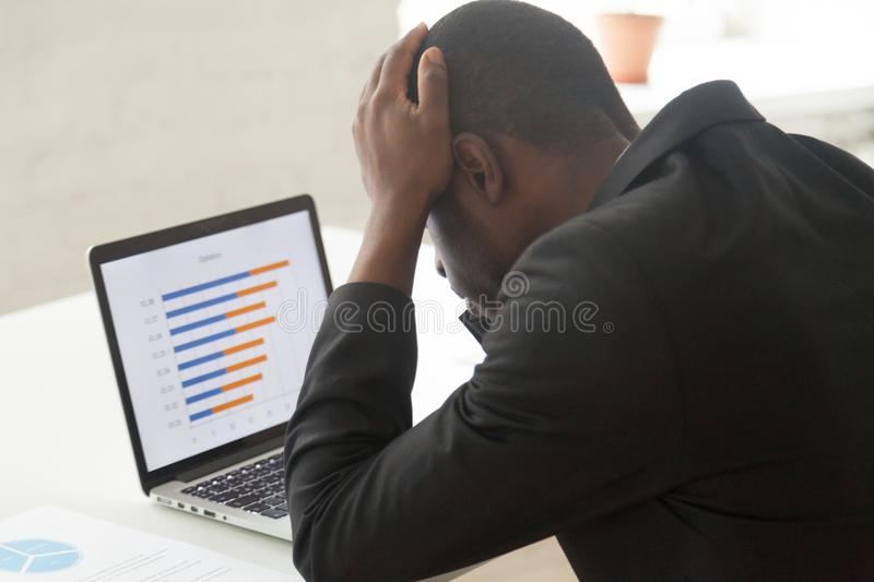 Stressed African American worker observing company business coll royalty free stock photos