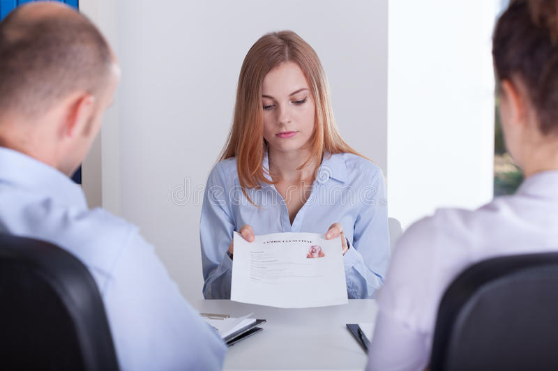 Stressed applicant and curriculum vitae. Young stressed female applicant giving her curriculum vitae stock photo