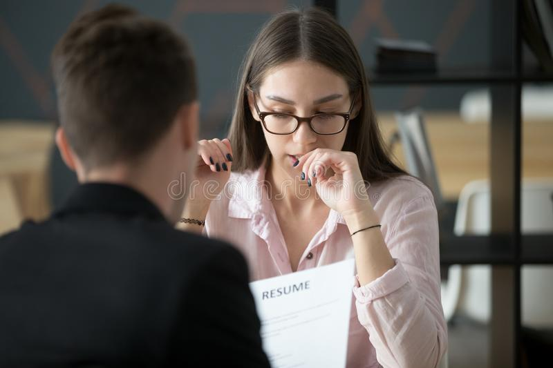 Stressed applicant nervous at job interview while hr reading res. Stressed young female applicant feeling nervous at job interview while hr reading resume royalty free stock image