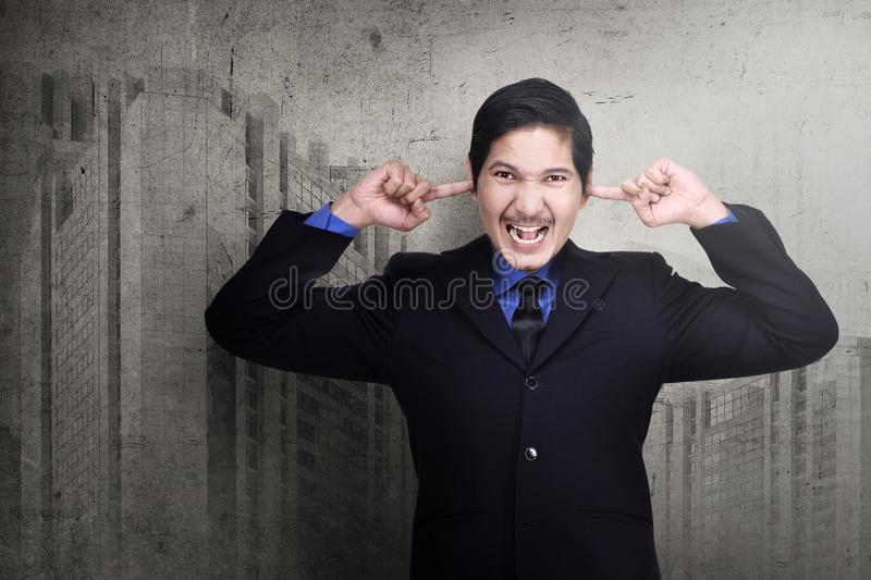 Stressed asian business man plugging his ears with fingers royalty free stock images