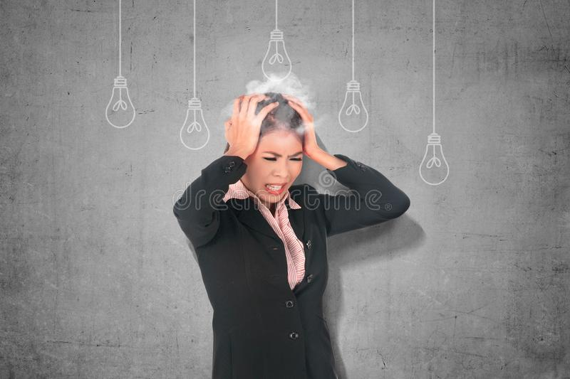 Stressed asian business woman thinking for new creative idea with light bulb hanging stock image