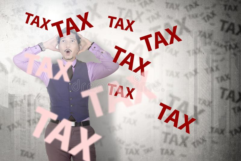 Stressed asian businessman looking at tax word. Taxes concept royalty free stock image