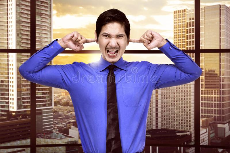 Stressed asian businessman plugging his ears stock image