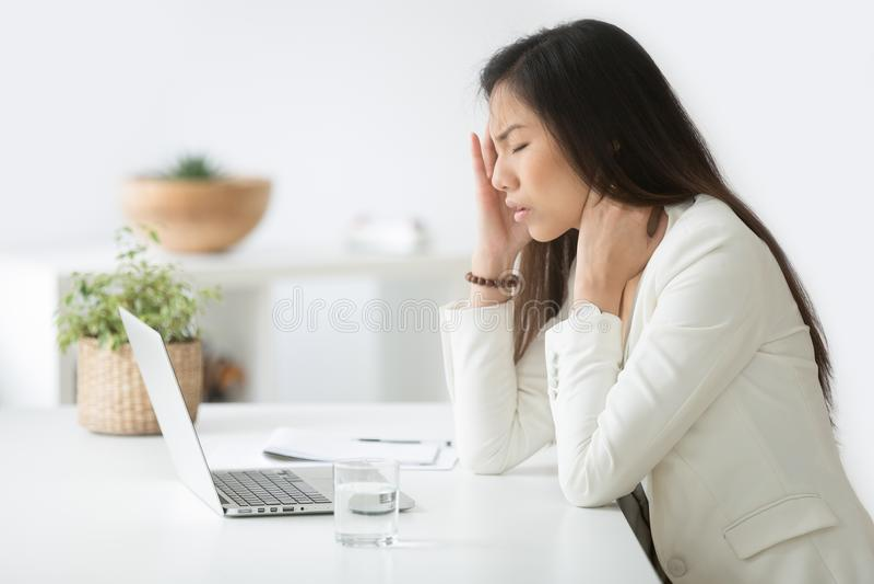 Stressed asian businesswoman having headache or migraine at work. Stressed asian businesswoman having headache at work concept, frustrated dizzy chinese woman stock photography