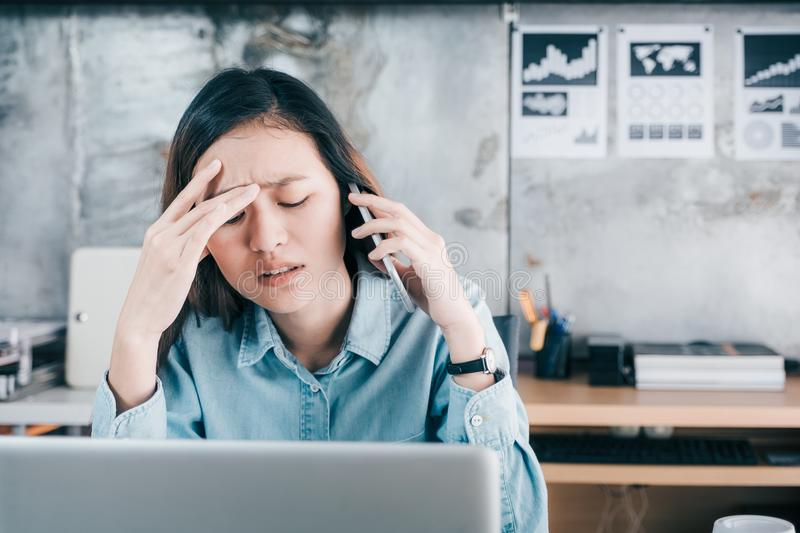 Stressed Asian creative designer woman cover her face with hand. And feel upset while talk on mobile phone with customer in front of laptop computer on desk at stock images