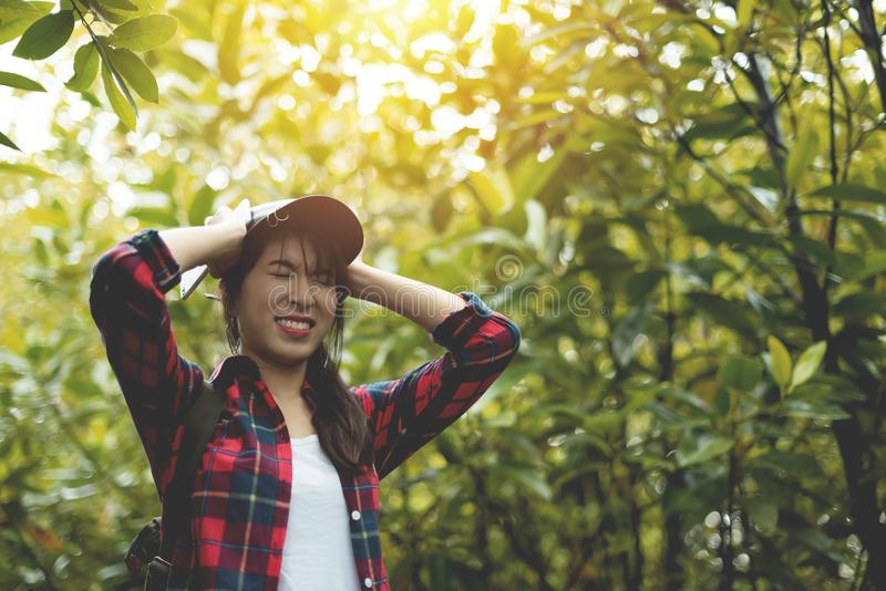 Stressed Asian girl traveler in red plaid shirt holding her head stock images