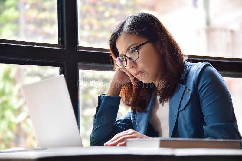 Stressed Asian glasses woman in blue shirt thinking. royalty free stock photography