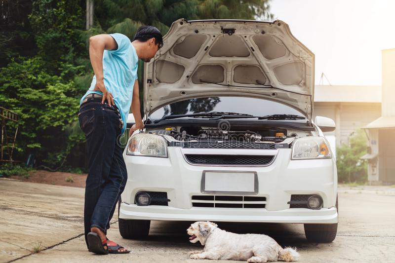 Stressed asian man looking at the engine of broken car with dog royalty free stock photo