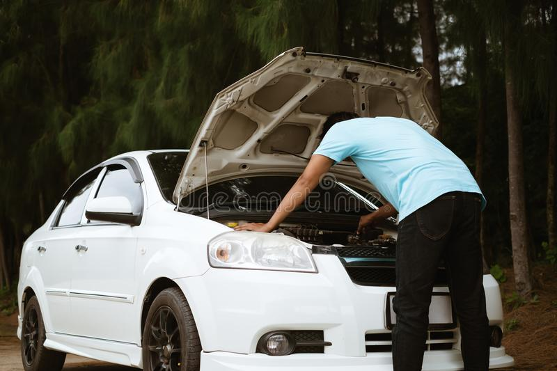 Stressed asian man looking at the engine of broken car royalty free stock photography