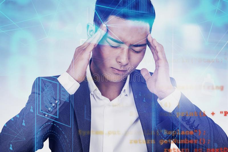 Stressed Asian man in suit, online security. Portrait of stressed Asian man in suite with double exposure of online security interface. Concept of fraud and stock photography