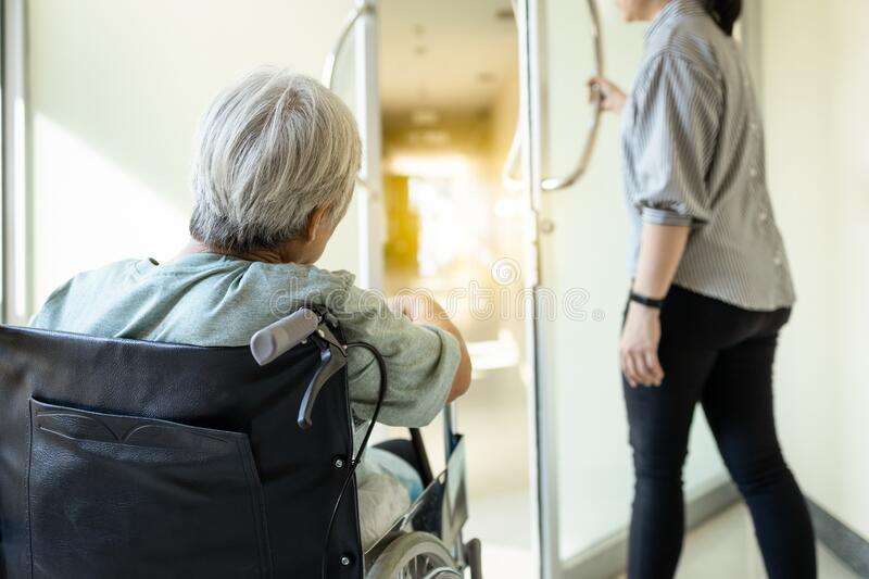 Stressed asian senior woman sit in wheelchair peeking out the door at hospital corridor,elderly patient feel afraid ,anxious to stock photography