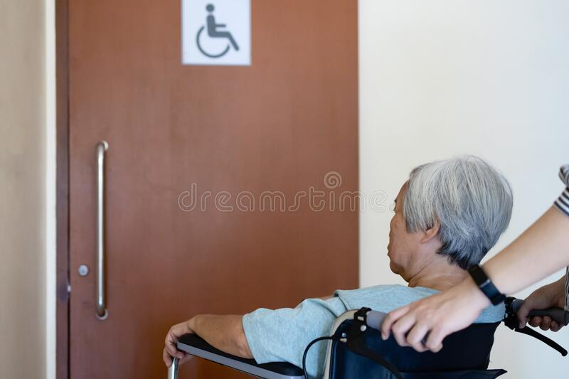 Stressed asian senior woman with wheelchair waiting on a long time at front disabled toilet,queue of disabled elderly waiting at royalty free stock image