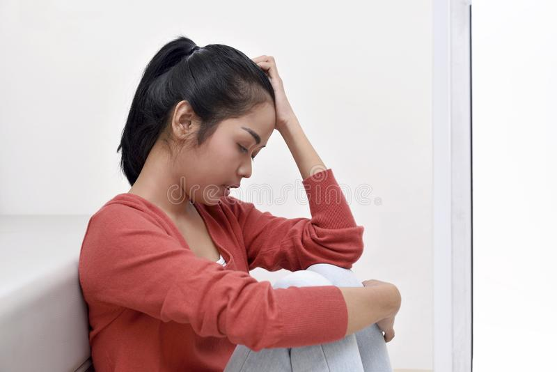 Stressed asian woman hugging her knee royalty free stock images