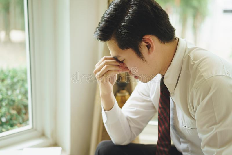 Stressed asian young businessman holding head with hands looking down. royalty free stock image